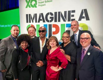 Cristina Alvarez (in red) and the Delaware Design Lab team receiving the XQ Super School award for educational innovation and excellence from famed rapper MC Hammer. (Photo courtesy of The Design Lab High School)