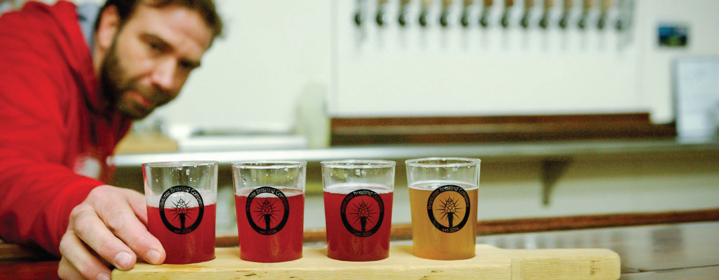 Craig Wensell, CEO and co-owner of Bellefonte Brewing Co., sets a flight of sour beers on the bar. Photo Anthony Santoro