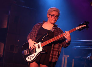 Izzi Sneider, 16, plays the bass during a performance with School of Rock. (Photo by Tim Hawk)