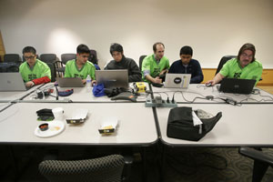 """Members of the program team work on the autonomous program, which will allow the robot """"ToMOEhawk"""" to run 15 seconds by itself. (Photo by Tim Hawk)"""