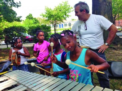 Children enjoy playing the vibraphone with Philly Vibe Duo and Harvey Price at Holloway Park. (Photo courtesy of The Grand Opera House)