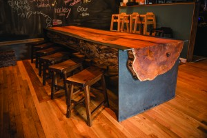 Pictured is a CP Furniture log table and benches installed at Grain Craft Bar + Kitchen on Main Street, Newark. (Photo by Carlos Alejandro)