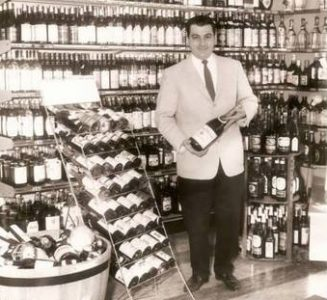 In 1963, Frank Gazzillo stands proudly in front of the store's new fine wine selection. (Photo courtesy of Peco's Liquors)