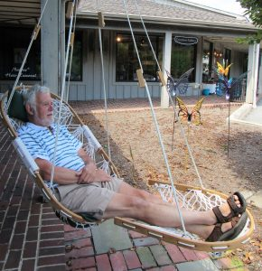 John Sherman, owner of Creations Gallery, sits on a hammock chair outside his shop. (Photo courtesy of Creations Gallery)