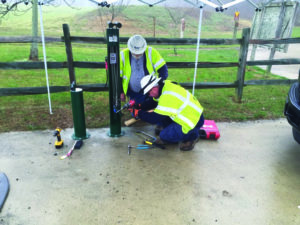 Delmarva Power workers installing bicycle pumps at White Clay Creek State Park. (Photo Courtesy of Friends of WCCSP)