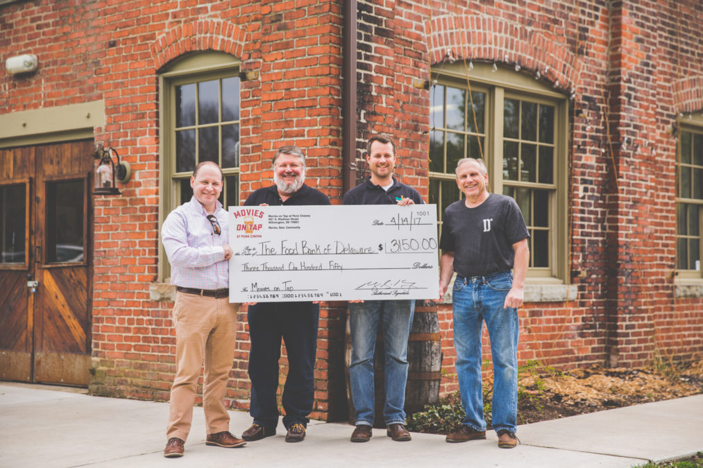 Ryan Kennedy of Premier Wine & Sprits (far left) and John Hoffman, owner of Dew Point Brewing Company (far right), award a check for $3150 to Mack Wathen and Larry Haas of the Food Bank of Delaware (both center). (Photo Ryan Kennedy, Premier Wine & Spirits)