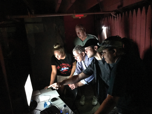 Alicia Lenoir, Mike Little, Andy Lendway (standing), Kyle McMahon and Fred Conkey watch the cameras set up at Frightland on a monitor at the central command center. Photo courtesy of the Diamond State Ghost Investigators (DSGI)